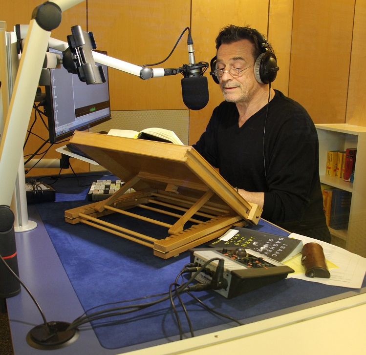 Das Bild zeigt einen Mann mit Brille und aufgesetzten Kopfhörern in einem schalldichten Raum. Er sitzt vor einem Lesepult mit aufgeschlagenem Buch und spricht in ein grosses Mikrofon.