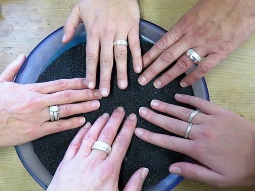 Fünf Hände mit Silberringen
